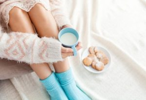 Soft photo of woman on the bed with cup of milk in hands, top view point