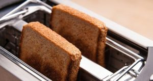 two hot bread toast in metal toaster